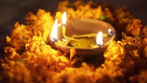 Traditional Indian lamps lit at night (Deepak Oil lamp) surrounded by orange marigold flowers (genda). Diwali.