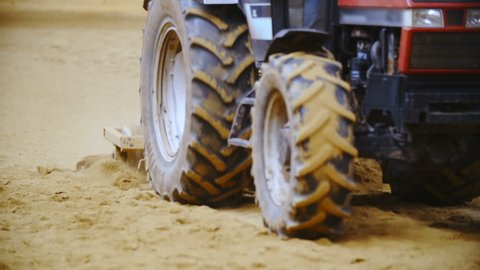 Tractor plow through sand close-up slow motion hd  long shot tracking  tractor plows in focus while it loosens the sand of riding arena  big  tractor tires