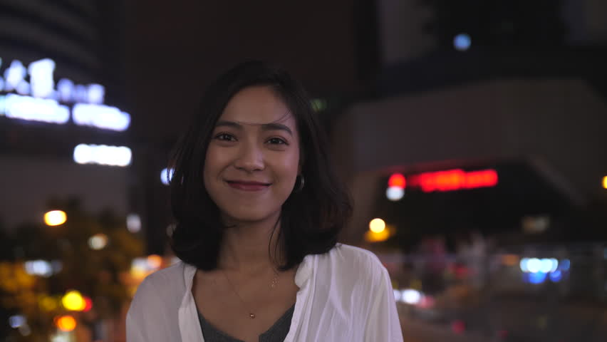 Slow motion of one beautiful young Chinese girl looking at camera smile in the summer night with wind blowing her hair city traffic and urban neon light at background,attractive young woman footage 4k