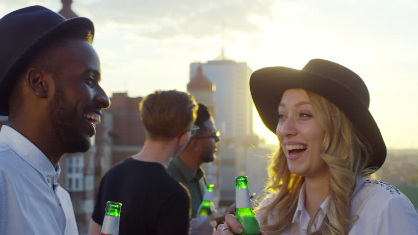 Young pretty woman and african american man in fedora hats holding beer bottles, laughing and dancing together at party with friends on urban rooftop at sunset