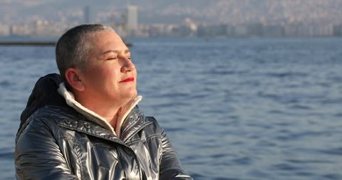 Happy middle aged cancer survivor after successful chemotherapy. Sitting near the sea at sunny winter day