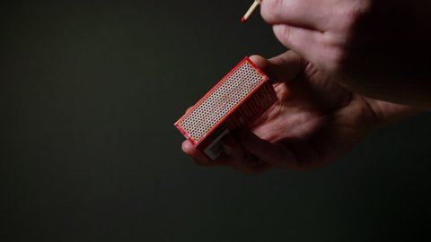 Male hand striking a matchstick against a matchbox in slow motion. Set against a dark background, with a high-contrast cinematic style.