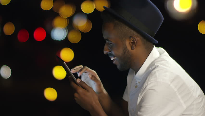 Side view of young african american man in fedora hat surfing the Internet on digital tablet and smiling while sitting on rooftop in the night; bokeh lights in the background