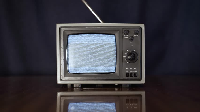 Old vintage TV switching on and off. Close-up static shot of small 70s style television showing white noise on vintage table display. | Shutterstock HD Video #1021732324