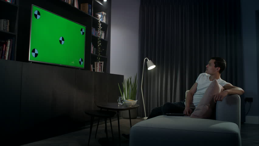 Young man relaxing on his sofa at night watching tv on his expensive large flat screen tv. Picks up the remote control and changes the channel | Shutterstock HD Video #1021744204