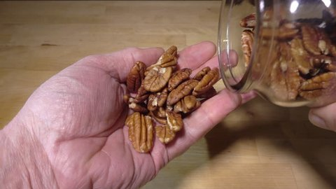 Slow motion close POV overhead shot of a man's hands holding a glass jar and shaking pecan nuts from it into the palm of his hand.