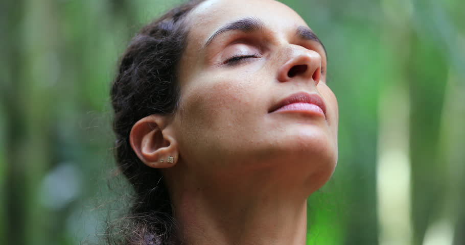 Woman with eyes closed taking a deep breath in meditation in nature | Shutterstock HD Video #1021758214