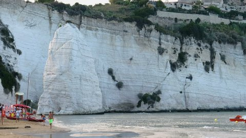 Gargano, Italy, 18 Aug 2018 - The Vieste beach in Gargano seacost with the scenic white Pizzomunno skerry rock at sunset