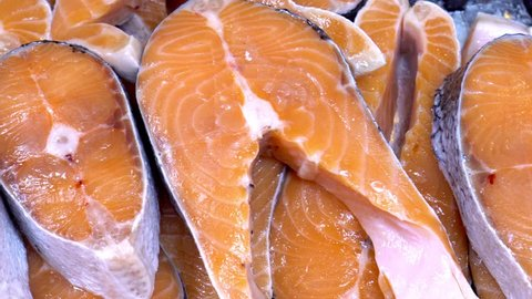 Salmon steaks and salmon fillet. Fresh salmon steaks and fillet are laid out on ice.