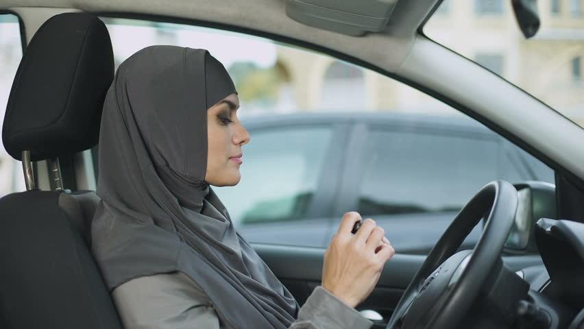 Attractive self-confident Muslim lady applying lipstick sitting in car, coquette   Shutterstock HD Video #1021904764