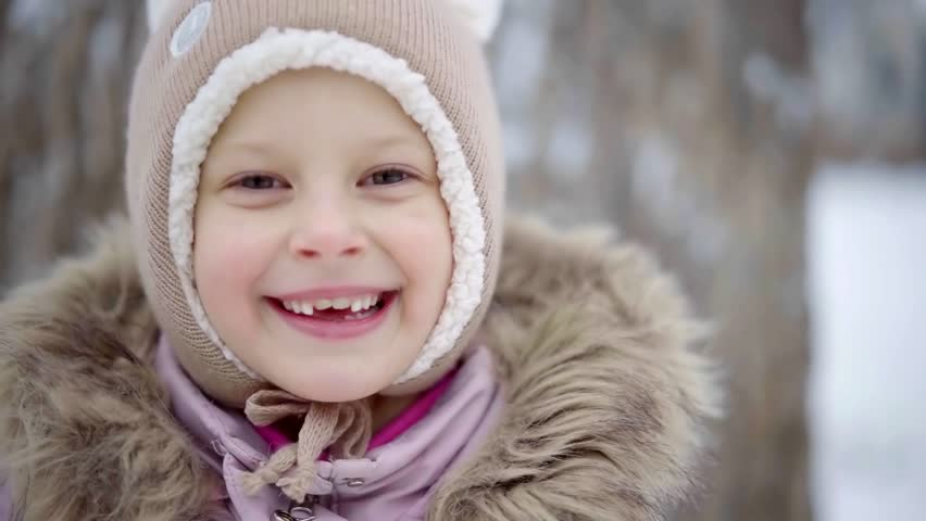 Face of little female preschooler close-up, she is smiling broadly, showing her new growing teeth | Shutterstock HD Video #1021917334