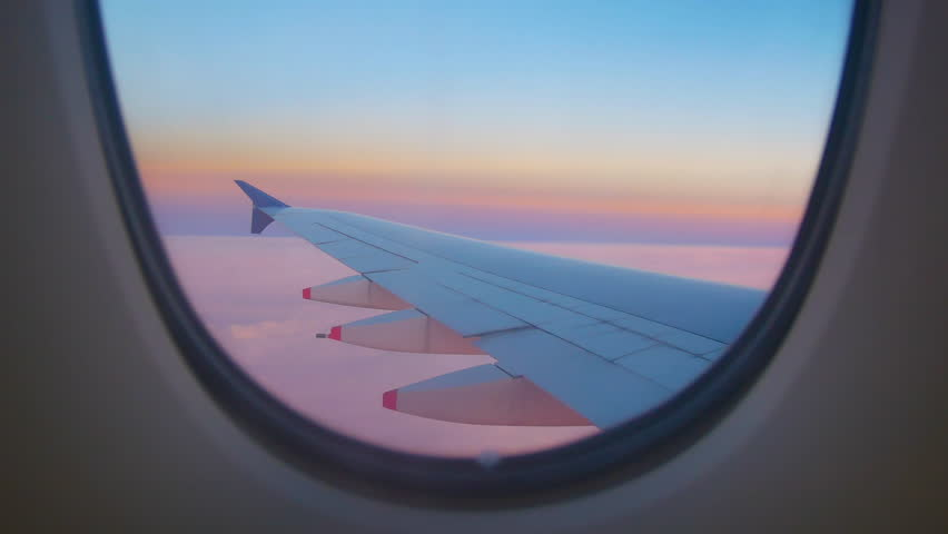 Travel Video View from the Airplane window seat. Twilight view in the early morning reduces speed and landing. Reduce the level of flight to destination with clouds and colorful sky background  #1021924384