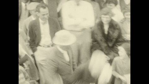 1920s: CANADA: man waves handkerchief. Passengers wait for boat. Passengers smile at camera.