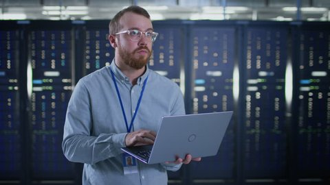 Bearded IT Specialist in Glasses is Working on Laptop in Data Center Next to Server Racks. Running Diagnostics or Doing Maintenance Work.