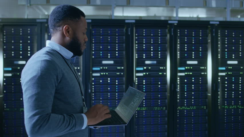 Black Data Center IT Technician Walking Through Server Rack Corridor with a Laptop Computer. He is Visually Inspecting Working Server Cabinets. | Shutterstock HD Video #1021974814