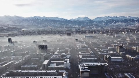 Shooting from a drone over the big city of Almaty. View of many roads, cars, people and large mountains. Places smog and fog. People walk the streets. Beautiful buildings with glass Windows. Trees.