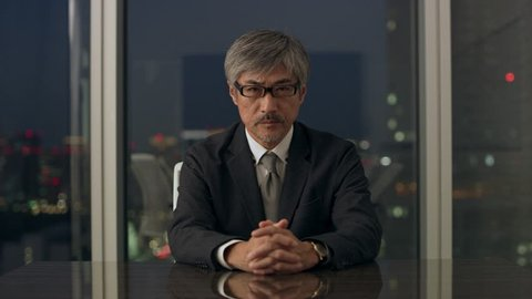 Professional Japanese man sitting at a conference table in front of a large window with a view of night time in a conference room with soft interior lighting. Medium shot on 4k RED camera on a gimbal.