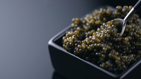 Black Caviar in spoon. High quality real natural sturgeon black caviar close-up. Delicatessen. Texture of expensive luxury caviar square dish on black. Seafood. 4K UHD video