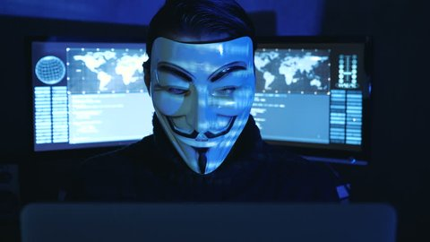 Cherkassy, Ukraine, January 04 2019: Hacker Anonymous in mask of Guy Fawkes Showing Fuck You in dark room filled with display screens.