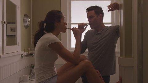 Handheld shot of happy couple brushing teeth in bathroom