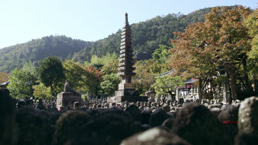 Young woman walking through a Buddhist shrine and looking around at the stone statues in Kyoto, Japan with bright day lighting. Wide shot on 4k  | Shutterstock HD Video #1022052664