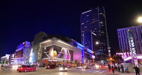 LOS ANGELES, CALIFORNIA - DECEMBER 9, 2018:  Night traffic and people walking near the Grammy Museum, ESPN Zone, L.A. Live, Microsoft Center and Ritz Carlton Hotel in Los Angeles, California, USA, 4K