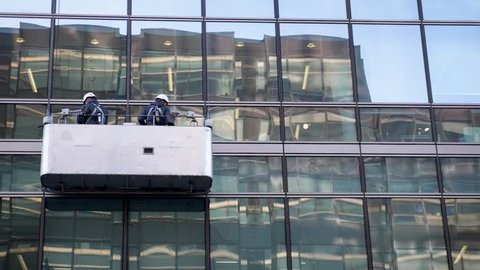 A pair of window cleaners harnessed into a cradle suspended on the side of a modern office building cleaning the exterior windows.