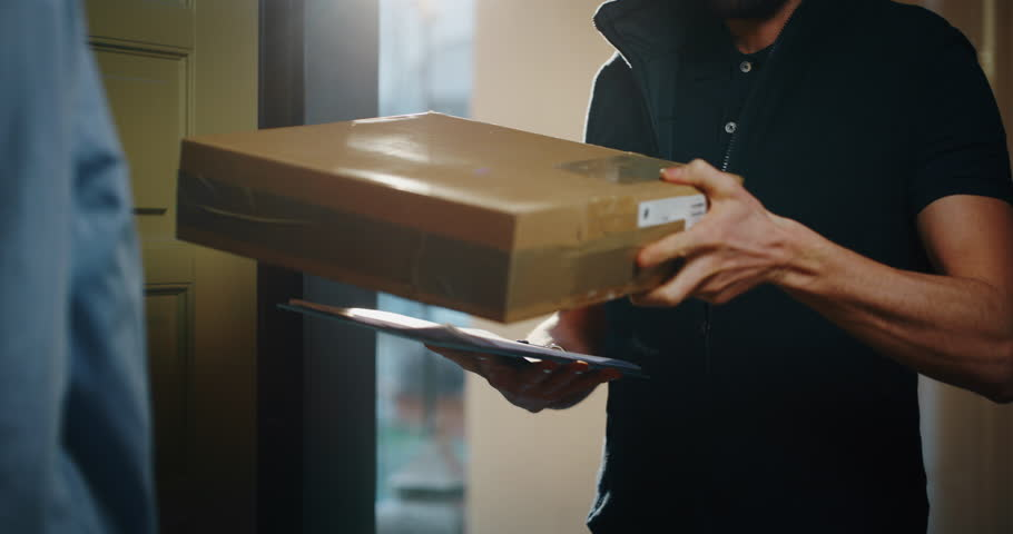 Happy young woman receiving and signing a parcel from mailman  delivered in her home. Shot with RED camera i 8K. Concept of courier, delivery, e-commerce, online shopping | Shutterstock HD Video #1022079664
