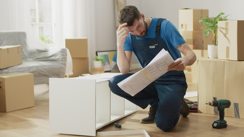 Successful Furniture Assembly Worker Uses Screwdriver to Assemble Shelf, Consults Instruction. Professional Handyman Doing Assembly Job Well, Helping People who Move into New House. | Shutterstock HD Video #1022087914