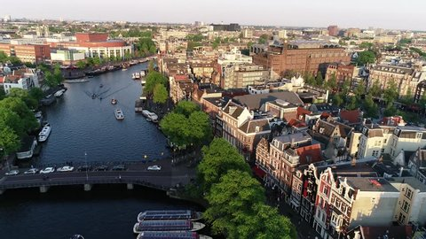 Amsterdam, Netherlands in 4K. Aerial view during sunset in late spring early summer.  Flying above canal and old centre district. Munttoren Bell Tower in background. Beautiful warm colors