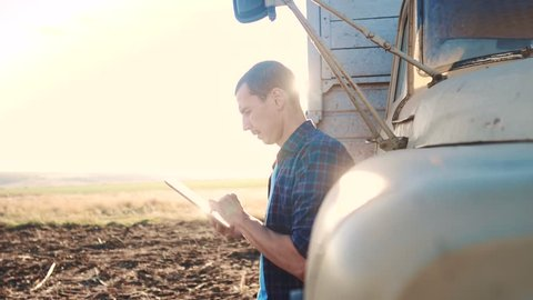 smart farming. man farmer driver stands with a digital tablet near the truck. slow motion video. Portrait businessman farmer standing in the field lifestyle harvesting season car. driver farmer uses a