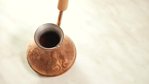Pouring water into traditional turkish copper coffee pot cezve