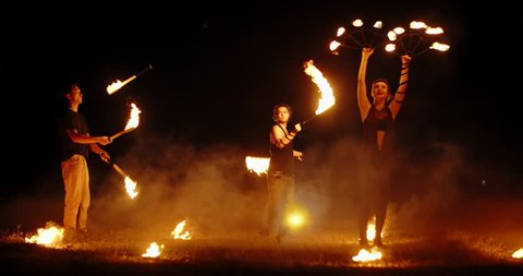 Three fire show performers standing in fire circle, performing. One juggles burning sticks, other flails them - slow motion 4k