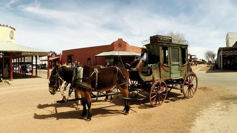Tombstone, AZ / USA - August 1, 2018: Zoom in shot of a stage coach tourist attraction. Clip reveals and Old West style transportation vehicle with horses and a driver adjusting his cowboy hat.