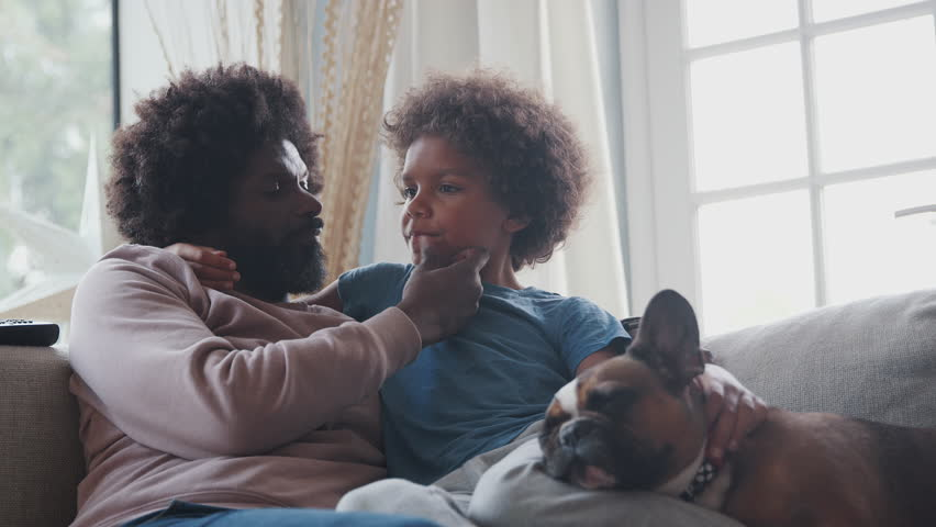 Caring middle aged black father and pre teen son reclining on sofa together watching TV with their sleeping pet dog, low angle, close up | Shutterstock HD Video #1022137204