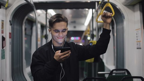 Happy businessman cheering celebrating looking at smartphone. Young urban professional successful business man receiving good news riding in public transport. He holds the handrail