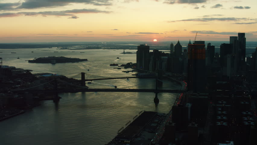 Aerial view of downtown Manhattan near the Upper Bay towards the Brooklyn Bridge, New York City, dark sunset light in winter. Wide shot. 4k shot with a RED camera.