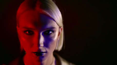 blonde woman with bright fashion make-up is posing for camera in darkness, red and blue spotlights