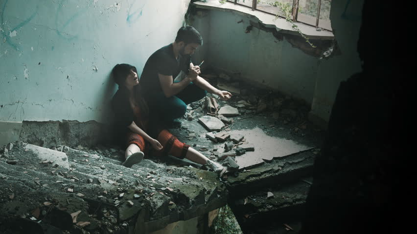 two guys (man and woman) taking drugs in an abandoned building