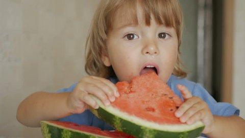 A little boy is eating a big watermelon. Portrait of child eats watermelon slices. 4K UHD.