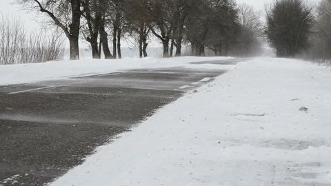 Winter road with lots of snow. Car on a snowy road. Bad winter road conditions. Curls the snow road. Wind with snow.