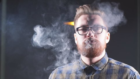Attractive man exhaling smoke from the nose. Man in glasses advertising a hookah. Slow motion