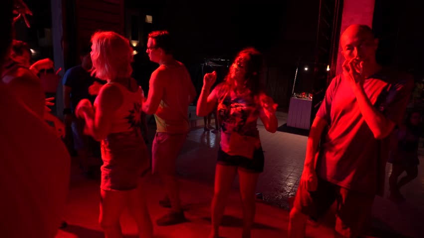 KOH PHANGAN, THAILAND - DECEMBER 22, 2018 : Girls and guys participate in Full Moon party in island Koh Phangan, Thailand. Crowds of people dance on the sandy beach during the full moon party #1022315224