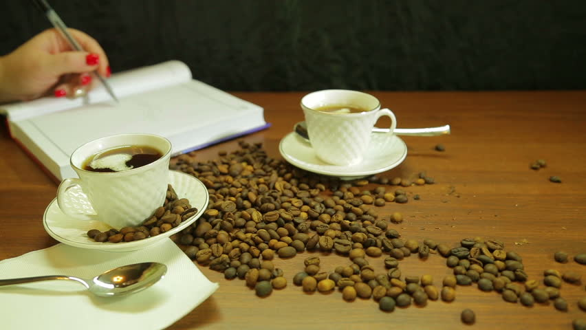Cups of strong coffee, a scattering of coffee beans on the table and a woman writes in a diary