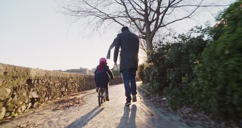 Daughter child girl learning riding bycicle with dad teaching in city.Growing,childhood,active safety family.Sidewalk urban outdoor.Warm sunset cold weather backlight.4k slow motion 60p back video