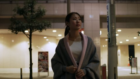 Medium shot on 4k RED camera. Beautiful, cheerful Japanese woman walking down a quiet alleyway past different shops and restaurants in downtown Tokyo at night with bright outdoor lighting.