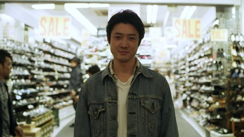 Portrait of a content Japanese man standing in front of a brightly lit store with people walking behind him on the street at nighttime. Medium shot on 4k RED camera.