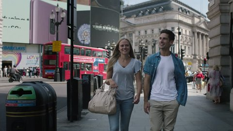 LONDON - JULY, 2018: happy young beautiful tourists walking in Regent Street in Piccadilly Circus in London. Handsome man and attractive blond sexy woman visiting the city along the streets.