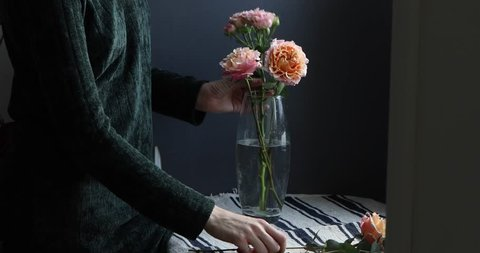 Female florist making flower arrangement of peony and shrub roses and eucalyptus branches in a vase on a dark grey background