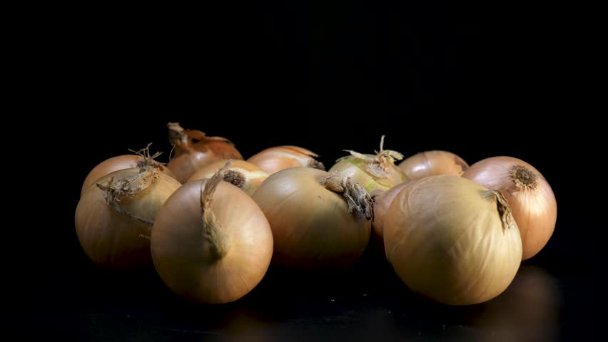 Yellow onions in close up rotates against black background | Shutterstock HD Video #1022480224